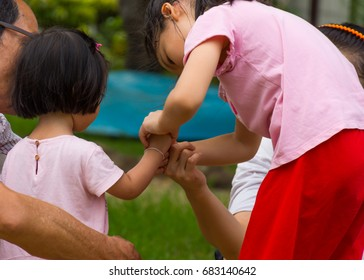 Little girl with her older sister Shaking hands in the garden