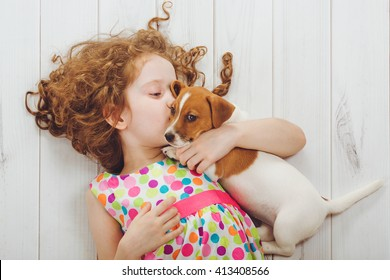 Little girl and her puppy whispers on wood background.