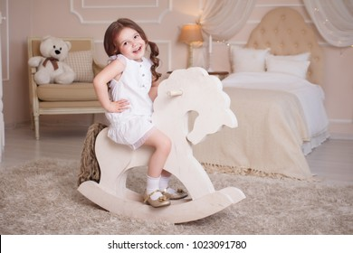 A little girl in her room, the bedroom rocks on a wooden horse. A child on a rocking-chair, in a white dress, laughs joyfully.