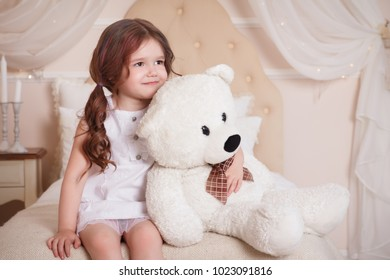 A little girl in her room sits on a bed and holds a bear. A child in a white dress with a toy. Beige interior.