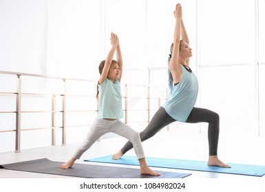 Little girl and her teacher practicing yoga in gym