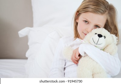 Little girl with her teddy sitting on the bed