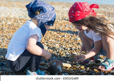 Little girl and her toddler sister in bandanas playing on the pebbly beach, looking at the starfish, selective focus