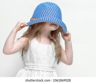 Little girl hides under her hat