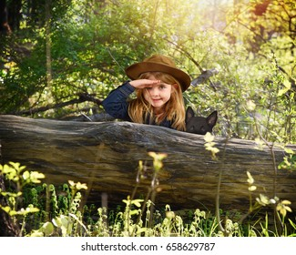 A little girl is hiding behind an old log in the woods with a hat and pet dog searching and playing for an imagination or exploration concept.