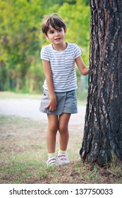 Little girl hiding behind a tree in the park.