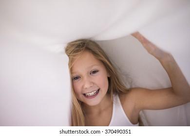 Little girl hiding under the sheet
