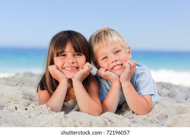 Little girl with his brother on the sand