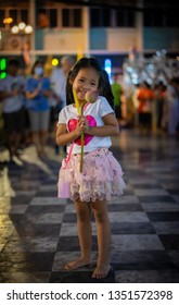 little girl hold the candle and lotus in hand for Buddhist ceremony around temple at night