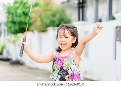 little girl holding badminton racquet and raise hand up for winner.Girl winner. little girl won the competition.Beautiful happy girl in a dress with a badminton racquet.