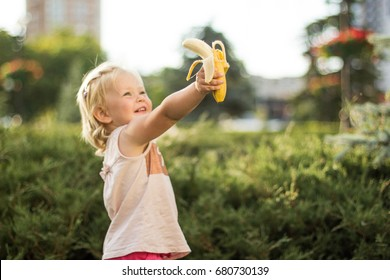 The little girl is holding a banana in her hand and laughing. Selective focus. A park.