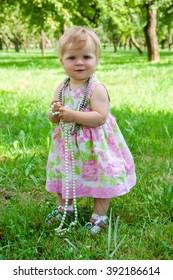 Little girl holding beads in hands in the garden in summertime