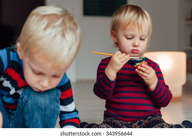 Little girl holding a brush and stamp of potatoes. Brother and sister.
