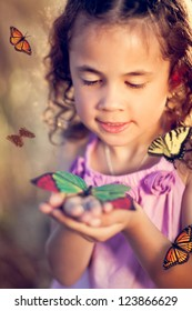 Little girl holding a butterfly in a field