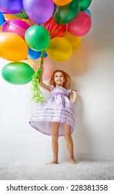 little girl holding color balloons