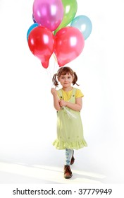 little girl holding colorful balloons on a white background