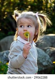 Little girl holding dandelion flower