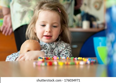 A little girl holding a doll at a table with a candy necklace on it.