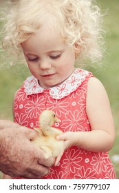 little girl holding duckling