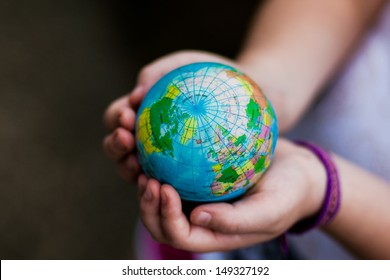 Little girl holding the earth in her hands. Earth day. Green concept