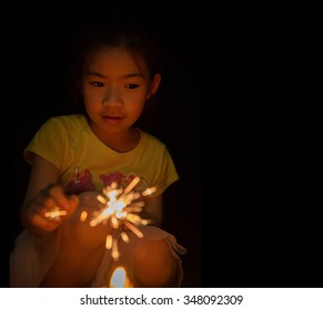 little girl holding fireworks on black background for new year holiday party
