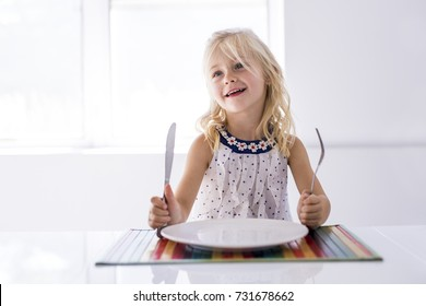 A Little girl holding fork empty plate ready for food.