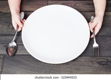 Little girl holding fork and spoon with , empty plate ready for food.