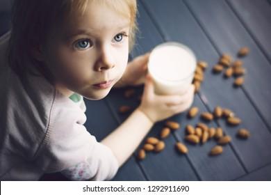 Little girl holding glass of vegan milk. Almonds milk.