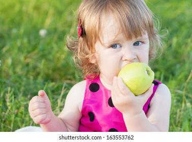 little girl is holding green apple