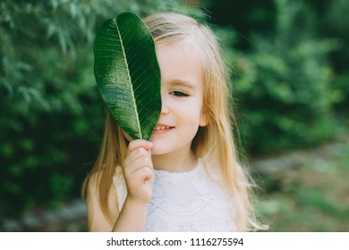 Little girl holding green leaf covering face, closeup