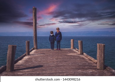 Little girl holding hands with her boy brother while standing on the wooden pier on the shore of Lake Ohrid, Northern Macedonia