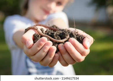 Little girl holding heap of dirt with earthworm on top