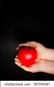 Little girl holding a heart. Close-up photo on black background. Copy space.