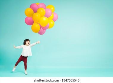 Little girl holding helium balloons on plain background