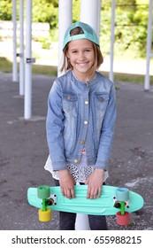 Little girl holding her blue skating board outdoor. Skateboard girl style.