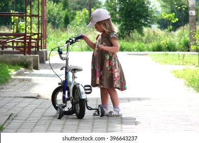 Little girl holding her children bicycle in summer day