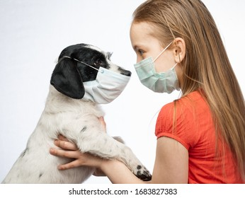 Little girl holding her dog both wearing protective surgical masks caring about her pet performing basic protective measures against transmission of coronavirus COVID-19 disease