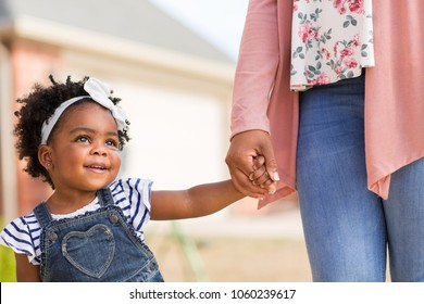 Little girl holding her mothers hand.