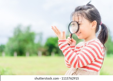 Little girl holding magnifying glass and check her hand for hands foot mouth disease.hand watch and germs on hands concept.