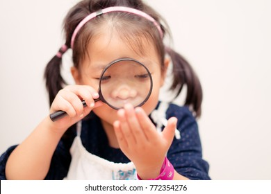 Little girl holding magnifying glass and check her hand for hands foot mouth disease.