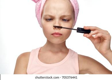 little girl holding mascara, cosmetics, baby.