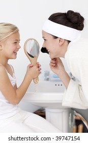 Little girl holding a mirror and mother putting makeup in bathroom