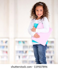 Little girl holding notebooks at the school library