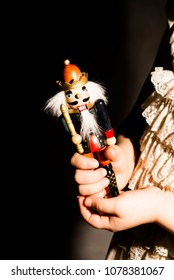 Little girl holding the Nutcracker. Close-up photo on dark background.