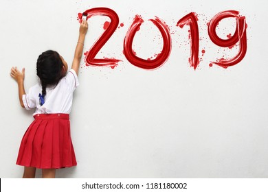 Little girl holding a paint brush painting happy new year 2019 on a white wall background, Back to school idea concept
