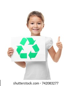 Little girl holding paper sheet with recycling symbol on white background