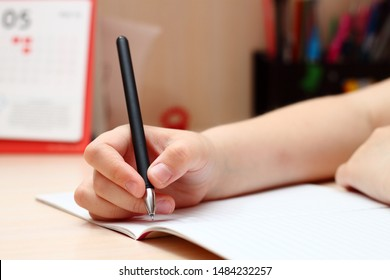 A little girl holding a pen and writing in a notebook. Close-up of the hand.