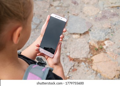 little girl holding a phone with broken screen while going to school