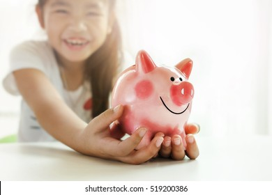 little girl holding a piggy bank while relaxing at home in a conceptual image.Selective focus to a cute pink piggy  bank