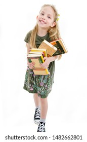 Little girl holding pile of school books grinning happily. Back to school concept. Isolated on white background